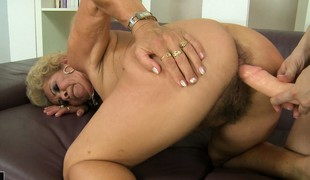 The bazaar cougar gets her hairy pussy drilled hard by the strap-on dildo and loves it