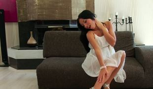 Black haired beauty in a white clothing seduces by stripping